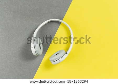Wireless funky modern gray headphones on illuminating yellow and grey background. Remote learning or listening to music or radio. Trendy lifestyle concept with copy space