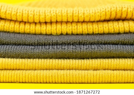 Colors of the year 2021 Ultimate Gray and Illuminating background. Gray and Illuminating winter hats on a yellow background. Clothing in design and color trend