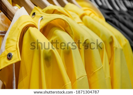 Yellow rain jackets hang on wooden hangers, closeup. Yellow and gray fashion background. Trendy Colors of the year 2021 Yellow Illuminating and Ultimate gray  Royalty-Free Stock Photo #1871304787