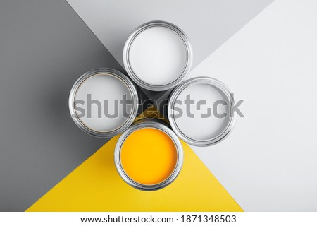 Demonstrating colors of year 2021 - Gray and Yellow. Four open cans of paint on bright symmetry background.Renovation concept.