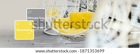 Hanging wicker chair, yellow cushions in minimalistic style outdoor interior. Demonstrating trendy Color of the Year 2021. Illuminating Yellow and Ultimate Gray. Duotone. Depression treatment. Banner.