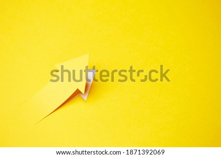 Right-up arrow cutted from solid sheet of yellow paper and curved up of one side with white paper underlay showing growth of stock market or up direction Royalty-Free Stock Photo #1871392069