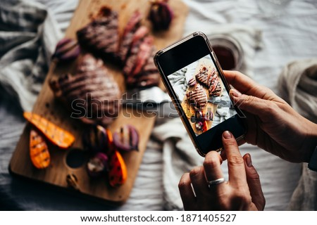 Taking a picture of some steaks and grilled vegetables with a mobile phone. Food photography or blogging concept