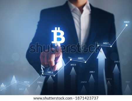 Businessman pointing digital bitcoin icon. Increase in value of cryptocurrencies. Futuristic stock exchange. Concept of the  rise in prices for bitcoin.