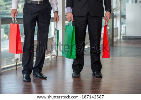Legs of two men holding paper bags in modern environment #187142567