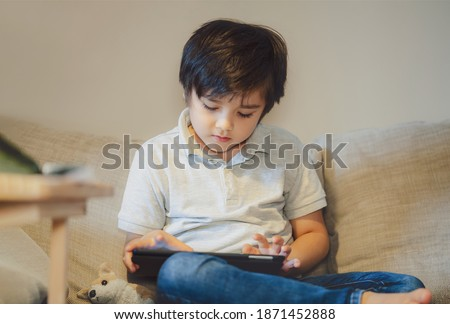 Indoor portrait Happy kid sitting on sofa watching cartoon on tablet, Cute boy playing game on touch pad, Child having fun and relaxing on his own in living room, New normal lifestyle