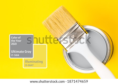 Open can of gray paint with white brush on it on yellow background. Top view. Repairing concept. Demonstrating colors of year 2021 - Gray and Yellow