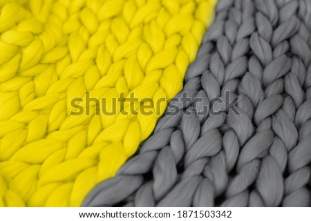 Trendy pantone colors of 2021- Illuminating Yellow and Ultimate gray texture blanket. Merino wool knitted plaid, toned creative background