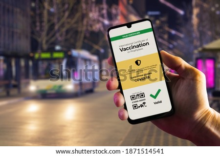 Smartphone displaying a valid digital vaccination certificate for COVID-19 in male's hand, downtown and city bus in background. Vaccination, disease immunity passport, health and surveillance concepts Royalty-Free Stock Photo #1871514541
