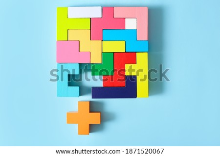 Concept of creative, logical thinking. Different colorful shapes wooden blocks on light background. Geometric shapes in different colors. Child development. Riddle and its solution. Logic tasks.