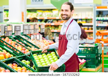 Supermarket clerk filling up apple storage racks in fruit department  #187153262