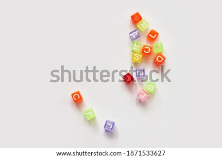 Different colorful letters on table. High quality photo. Cube shape. Typography design. Message broken. Label concept. Constructor for lettering. Copyspace. Light grey background
