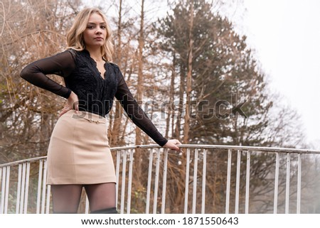 Pretty blonde girl posing on the bridge.The picture has a white balance effect.