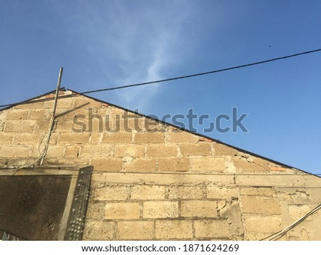 a close up view of a brick  house with a blue sky backdrop