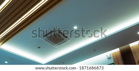 Selective focus on cassette type air conditioner mounted on ceiling wall. Air duct on ceiling in hotel. Air heading unit on gypsum wall. Cool system in the building. Air flow and ventilation system.  Royalty-Free Stock Photo #1871686873