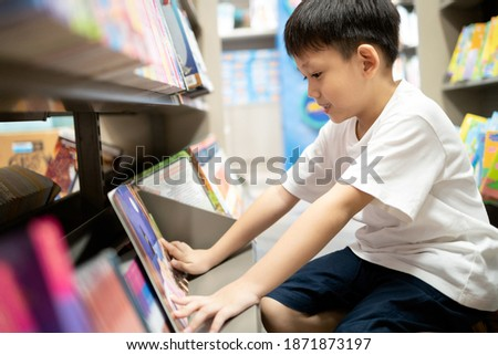 Asian little child reading a cartoon from favorite comic book on bookshelf at bookstore,happy kid boy enjoying learning in school library,brain development,education,reading skills in childhood