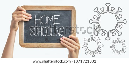 HOME SCHOOLING Background Banner - Blackboard with wooden frame held by children's hands isolated on white background and white chalk lettering and Cartoon virus, with space for text