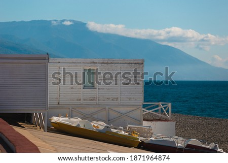 Multicolored boats stand on the shore near the dock on a bright sunny day against the backdrop of mountains and the sea
