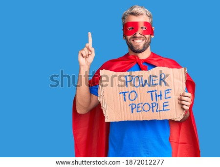 Young blond man wearing super hero custome holding power to the people cardboard banner surprised with an idea or question pointing finger with happy face, number one
