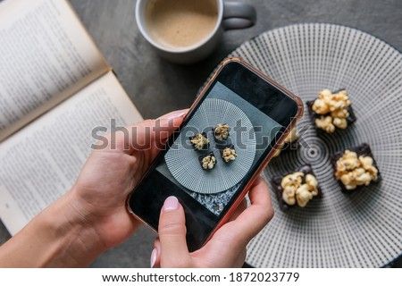 Close up of hands with smartphone taking picture of dessert food. People, leisure, eating and technology concept