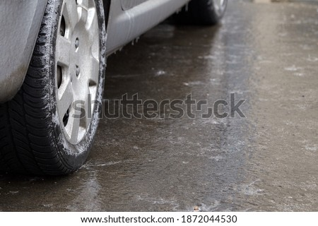 Ice crusted ground, car wheel on icy road, hazardous weather conditions, winter street Royalty-Free Stock Photo #1872044530