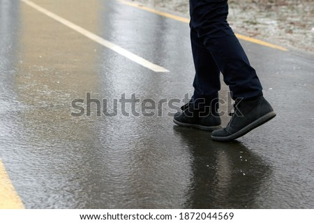 Ice crusted ground, a man walking on a slippery street, icy sidewalk, winter weater Royalty-Free Stock Photo #1872044569