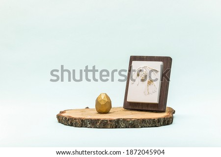 Trendy Easter lowpoly decor for design. Botanical bas-relief pine branch with cone on wooden platform and golden egg of geometric style. Happy Easter greeting card. Modern and luxury interior of room