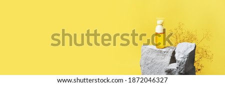Banner, header with Serum cosmetic pump bottle on Ultimate Gray concrete stone podium on Illuminating yellow background. 2021 color of the year template. Trendy beauty product concept, copy space
