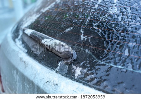 Car window and windscreen wiper in ice after freezing rain. Freezing rain, anomalies of nature. Soft focus technique Royalty-Free Stock Photo #1872053959