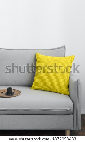 Illuminating yellow and ultimate Gray - trendy colors of the year 2021 in interior. Gray sofa with yellow pillow in modern scandinavian style room interior. Vertical crop for social media, copy space