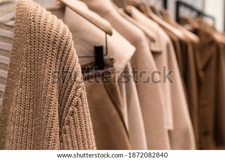 Coat and sweater light brown on the hanger in the store. Classic women's fashion clothes. Royalty-Free Stock Photo #1872082840