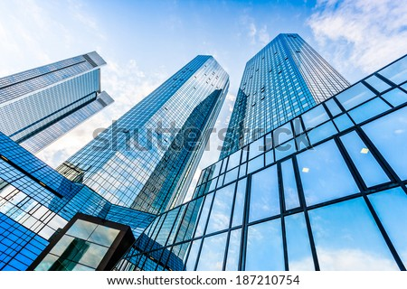 Bottom wide angle view of modern skyscrapers in business district with blue sky and clouds #187210754