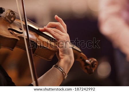 Hand on the strings of a violin Royalty-Free Stock Photo #187242992