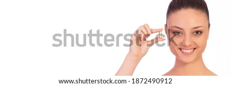 Selective focus, collagen capsule. Girl holding fish oil capsule on white background horizontal banner. Concept of health and supplements and vitamins