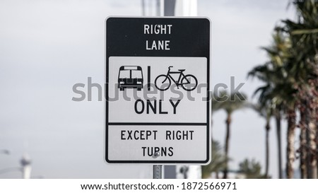 A lane restriction traffic sign indicating right lane is designated for bus and bicycles except when making right turns. Found on W. Sahara Avenue in Las Vegas, Nevada, USA. #1872566971