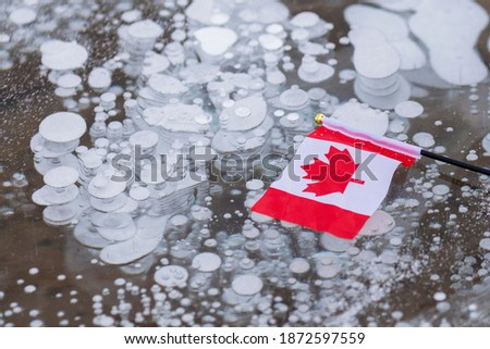 Horizontal photo of Canadian flag and frozen methane bubbles in Abraham lake ice in Alberta Canada