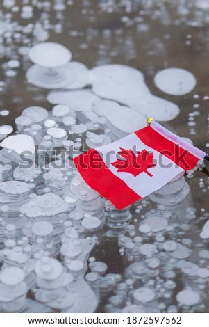 Vertical photo of Canadian flag and frozen methane bubbles in Abraham lake ice in Alberta Canada