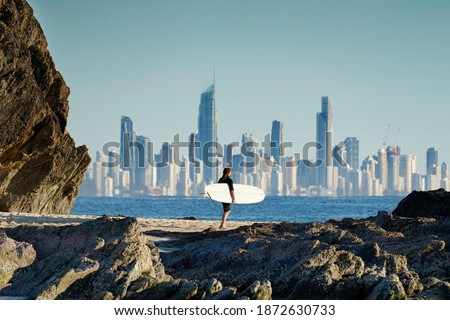 Surfer walking along a rocky coastline with the Gold Coast city skyline in the background. Royalty-Free Stock Photo #1872630733