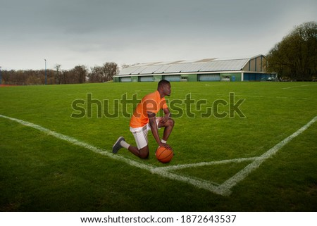 lonely ballplayer on grass during lockdown Royalty-Free Stock Photo #1872643537
