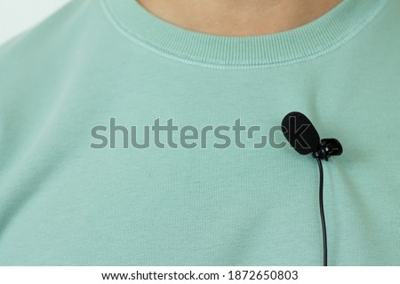 Small lavalier microphone or mic buttonhole on a man's t-shirt closeup