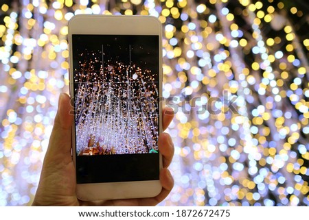 Hand holding mobile phone and take photo of christmas tree with decoration and ligthing. Technology and holiday concept.