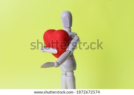 A wooden mannequin holds a heart in his hands on a yellow background. Copy space. Love and Valentine's Day concept. Wooden mannequin with a red heart.