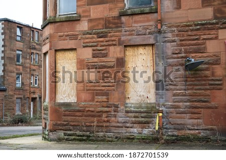 Derelict council house in poor housing estate slum with many social welfare issues in Port Glasgow Royalty-Free Stock Photo #1872701539