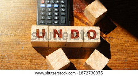 Undo word on wooden cubes with letters, and calculator. Lifestyle and state of mind concept. #1872730075