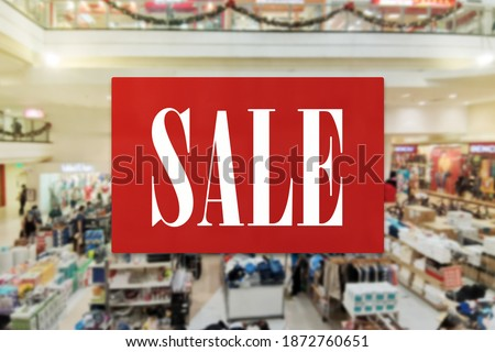 A sale announcement sign with a mall atrium backdrop. Shopping opportunity, discount and promo concept