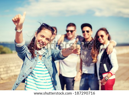 summer holidays and teenage concept - teenage girl in sunglasses and headphones hanging out with friends outside and showing thumbs up #187290716