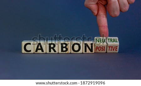 From carbon positive to neutral. Hand flips cubes and changes words 'carbon positive' to 'carbon neutral'. Beautiful white background, copy space. Business, ecological and carbon neutral concept. Royalty-Free Stock Photo #1872919096