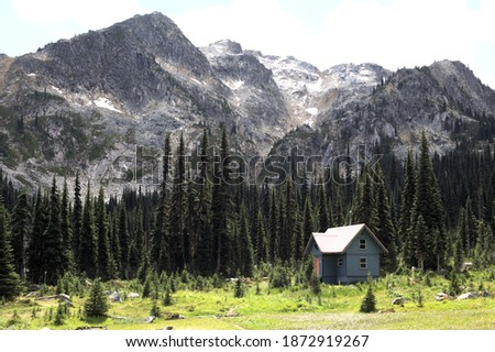 A view of the Brian Waddington hut, a sanctuary for hikers who explore this stunning wild and remote Canadian natural landscape of alpine mountains, green conifers, and blue lakes Royalty-Free Stock Photo #1872919267