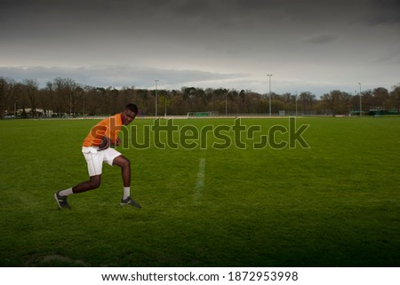 lonely ballplayer on grass during pandemic lockdown Royalty-Free Stock Photo #1872953998
