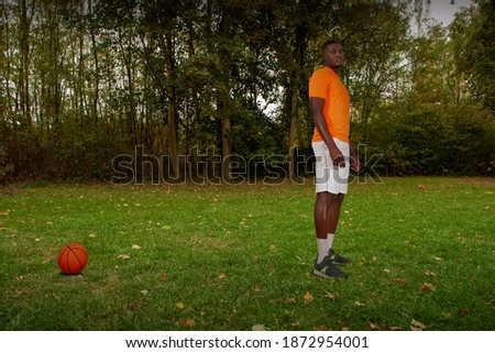lonely ballplayer on grass during pandemic lockdown Royalty-Free Stock Photo #1872954001